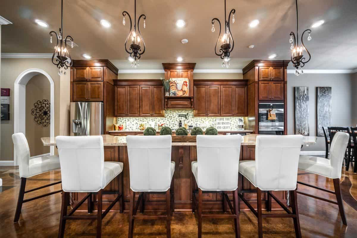 Kitchen with wooden cabinetry and a center island complemented with ornate pendants and white leather counter chairs.