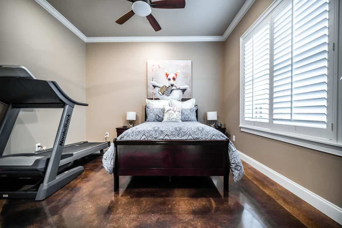 This bedroom is filled with a ceiling fan, a treadmill and a dark wood bed under the lovely dog painting.