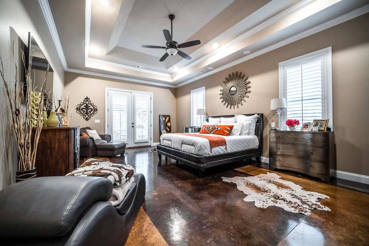 The primary bedroom has a stunning step ceiling, a sitting area, and a dark tiled flooring topped with a cowhide rug.
