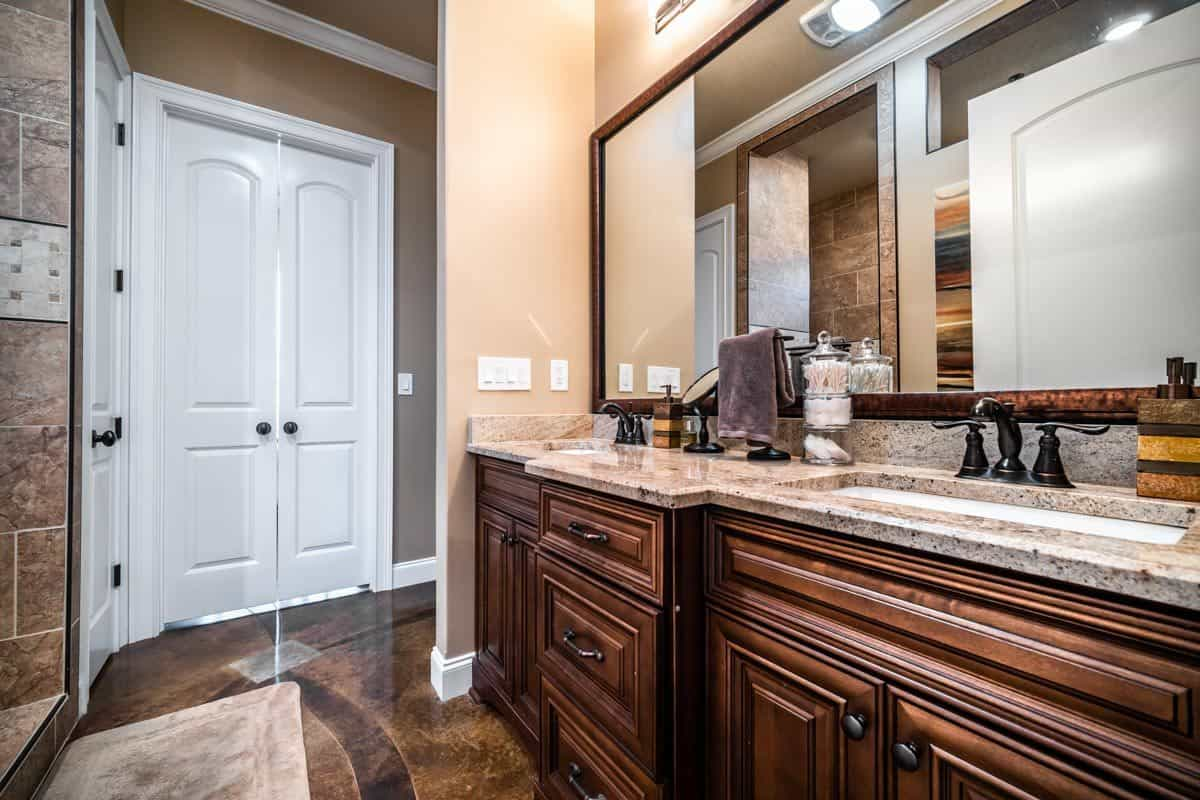 The primary bathroom features a dual sink vanity paired with and a large rectangular mirror.