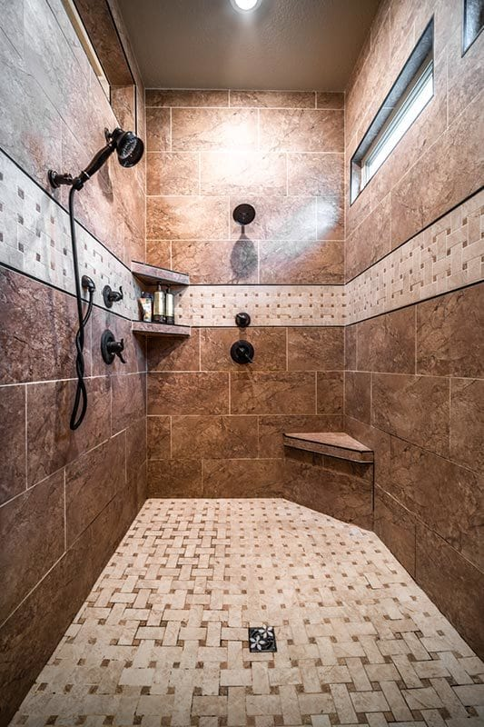 There's also a walk-in shower with a tiled corner seat and shelves along with wrought iron fixtures.