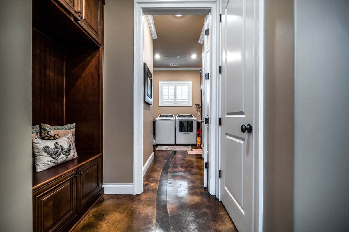 Utility room with dark wood cabinets and top load appliances over the brown flooring.