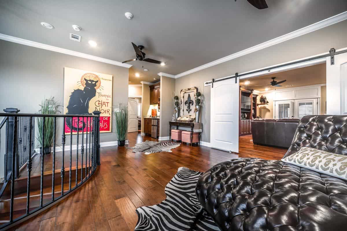 Second-floor loft with a leather tufted seat and zebra rugs laying on the rich hardwood flooring.