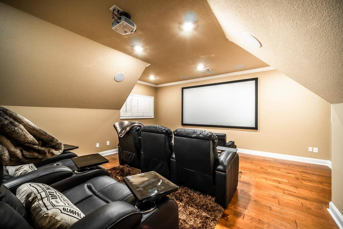 Home theater with a brown shaggy rug and black leather recliners facing the projector screen that's fixed against the beige walls.