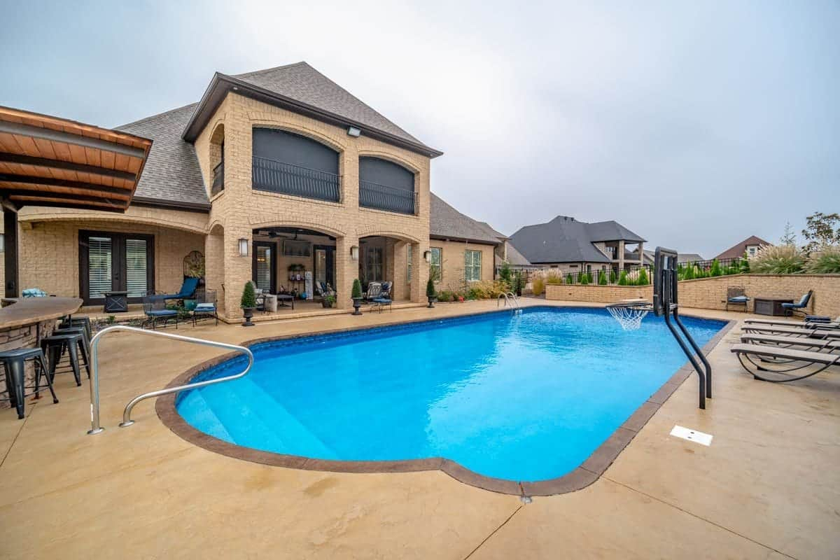 Outdoor living with multiple sitting areas and a stunning pool with a mini-basketball ring.