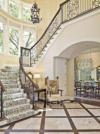 Foyer with a classy armchair and a winding staircase with intricate detailing.