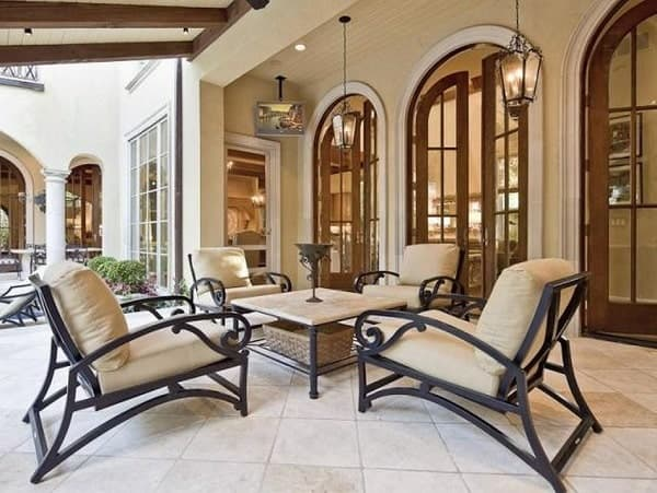 Outdoor living filled with beige cushioned sits and a metal center table topped with antique goblet.