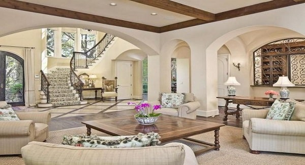 The den is defined by open archways and a beige ceiling framed with rustic wood beams.