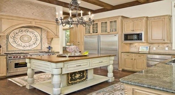 The kitchen features a cooking alcove and a light wood center island under the ornate candle chandelier.