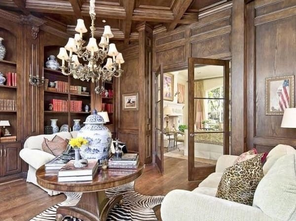 Study with coffered ceiling and built-in bookcases matching with the paneled walls and hardwood flooring.