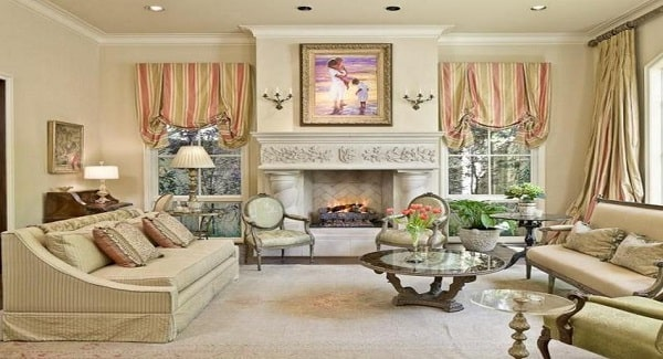 Living room with beige seats and a marble fireplace adorned with a lovely painting.