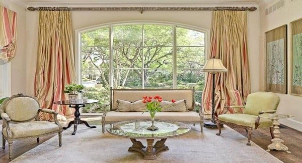 This view shows the massive arched windows behind the beige sofa dressed in elegant striped draperies.