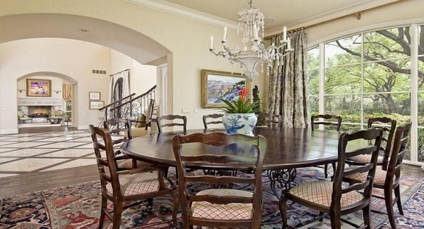Formal dining room with a round dining set and large paneled windows overlooking the outdoor scenery.