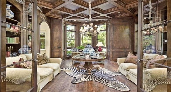 The study is filled with an elegant chandelier, beige sofas, and a round center table over a zebra rug.