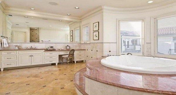 The primary bathroom features a long vanity and a circular soaking tub clad in elegant marble.
