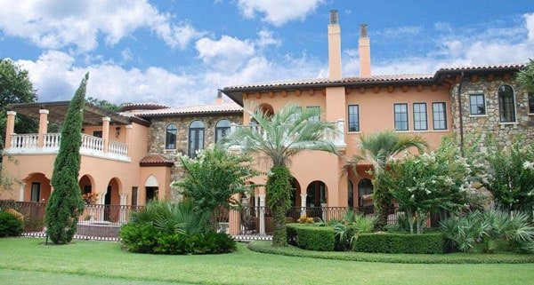 Home exterior view concealed by tall plants showcases clay tile roof, brick accents, decorative columns, and arches.