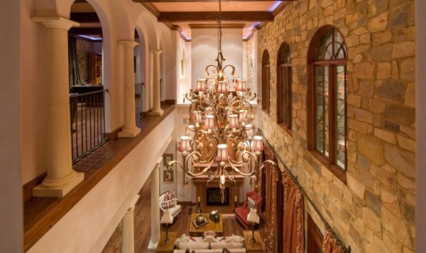 Second floor balcony overlooking the living room. It is lit by a grand chandelier hanging from the beamed ceiling.