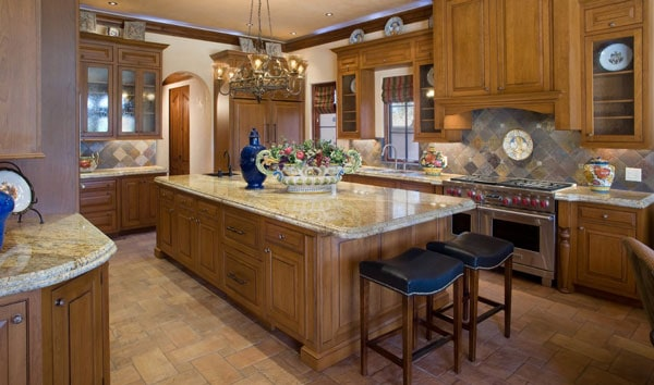 Kitchen with wooden cabinetry matching the granite top central island complemented with a pair of bar stools.