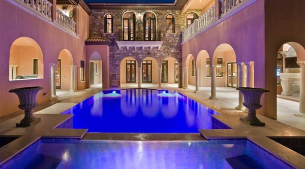 The courtyard features a stunning pool surrounded with archways and flanked by decorative flower pedestals.