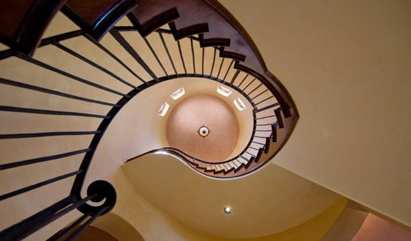 View of the winding staircase and a dome ceiling from below.
