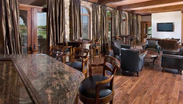A family room filled with plenty of black leather seats, round wooden tables, and a bar on the side.
