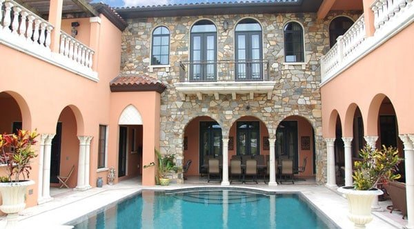 Courtyard during daylight with a swimming pool and multiple seating areas inside the archways.