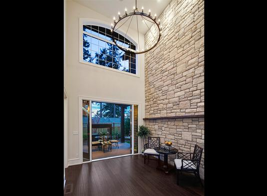 The two-story sitting area has a brick accent wall and sliding glass doors that lead out to the outdoor living.