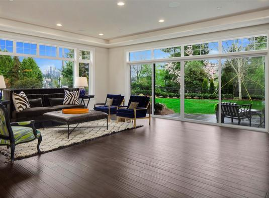 The living room has natural hardwood flooring and full-height glazing overlooking the serene outdoors.