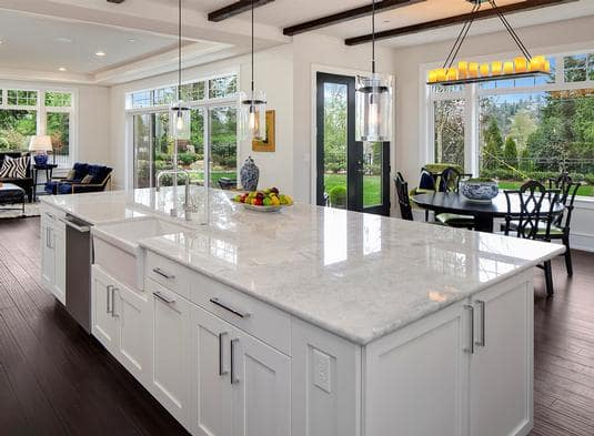 A closer look at the central island shows the granite countertop and a farmhouse sink paired with chrome fixtures.