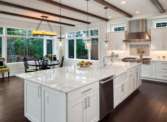 The central island faces the breakfast nook that's filled with a round dining set and a warm linear chandelier.