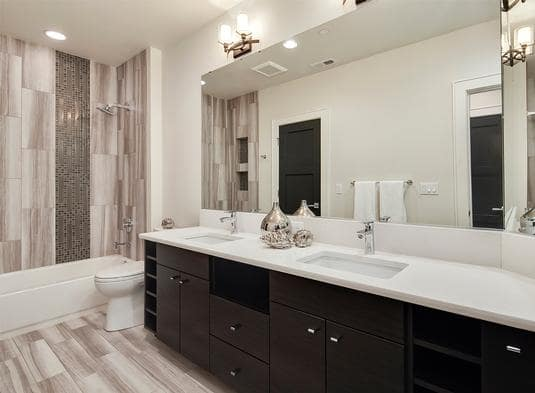 Bathroom with a dual sink vanity, a toilet, and a tub and shower combo accented with black mosaic tiles.