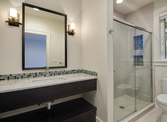 This bathroom offers a toilet, walk-in shower, and a sink counter paired with a wooden framed mirror.