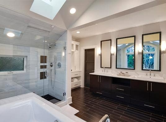 The primary bathroom is equipped with a deep soaking tub, a walk-in shower, and dual sink vanity lit by glass sconces.