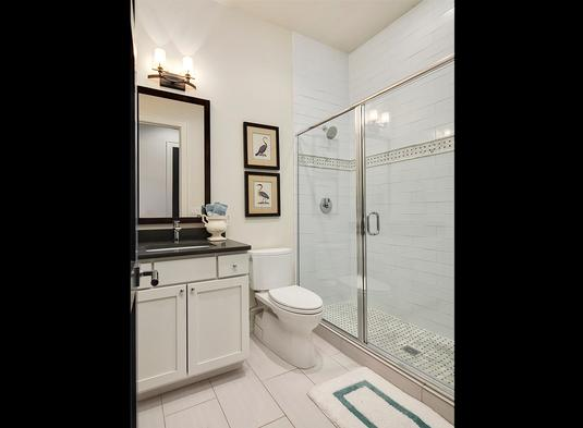 Bathroom with walk-in shower and sink vanity flanking the toilet under the framed artworks.