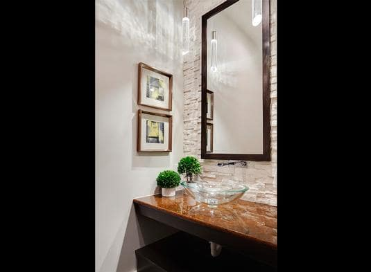 Powder room with a rectangular mirror and an elegant granite counter topped with a glass vessel sink.