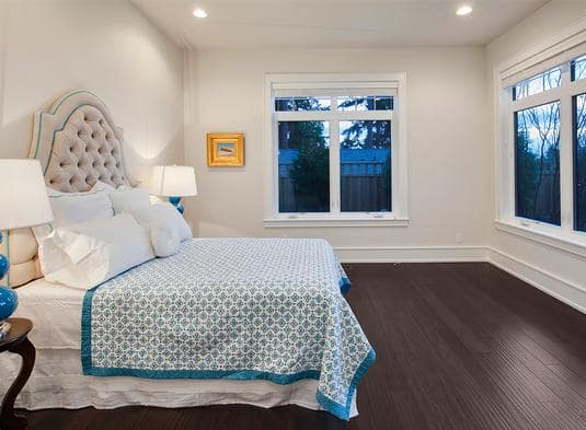 Bedroom with dark hardwood flooring and a beige tufted bed covered in a patterned blanket.