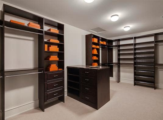 Walk-in closet with built-in shelves and rods along with a peninsula that's topped with a black granite countertop.