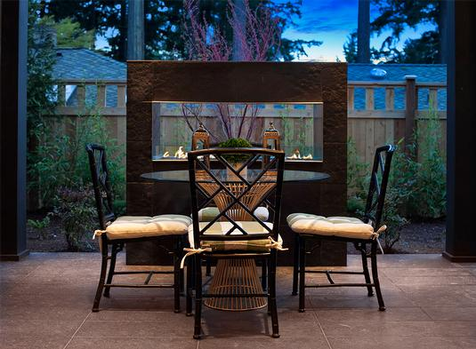 Outdoor living space with a modern freestanding fireplace and a glass top dining table surrounded by cushioned chairs.