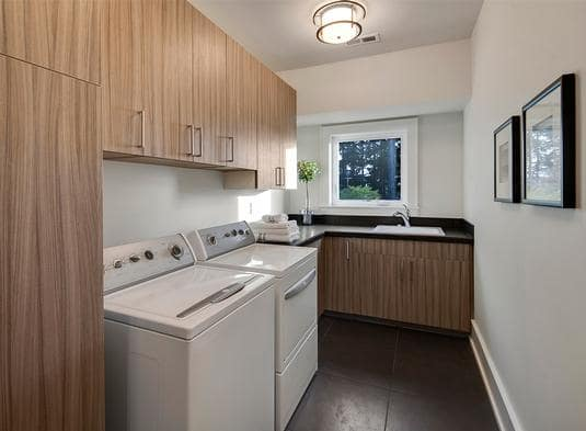 Laundry room with washing machine, dryer, and wooden cabinets that contrasts the white walls.