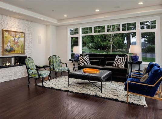 Living room with a black velvet sofa and vibrant armchairs paired with a leather ottoman.