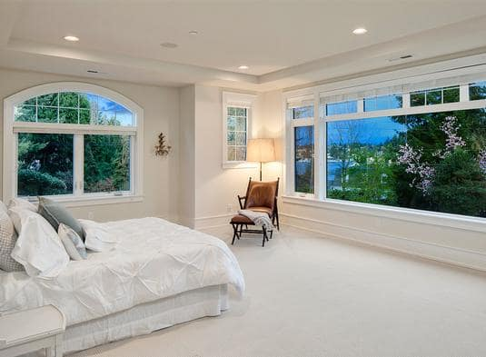 Primary bedroom with a beige carpet flooring and a tray ceiling fitted with recessed lights.