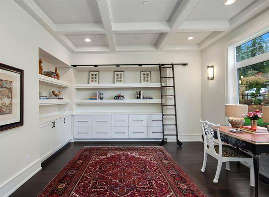 Home office with inset shelves, coffered ceiling, and a dark hardwood flooring topped by a red area rug.