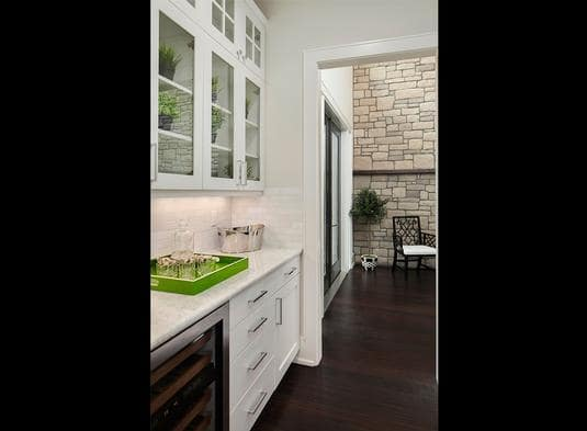 Butler's pantry with glass front cabinets, white drawers, beverage fridge, and a marble countertop.