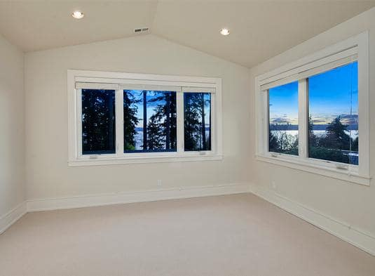 Empty room with beige carpet flooring, white-framed windows, and a cathedral ceiling fitted with recessed lights.