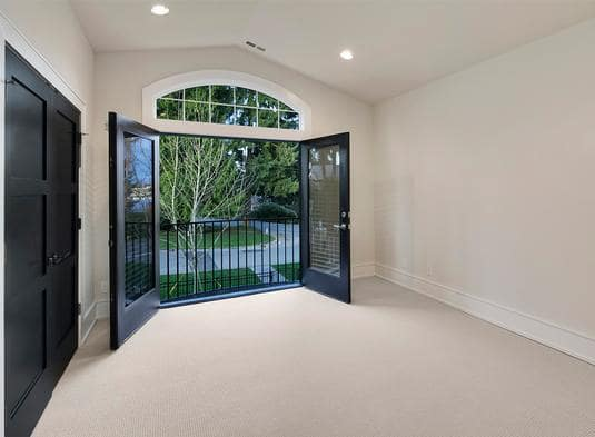 Upper balcony with wrought iron railings and a french door under the arched transom window.