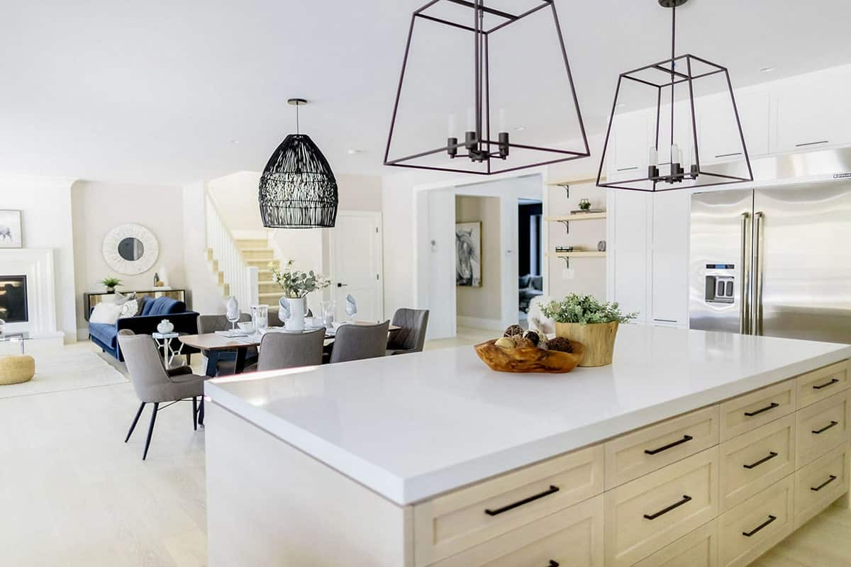 A closer look at the eat-in kitchen with a large island bar under a pair of oversized cage pendants.