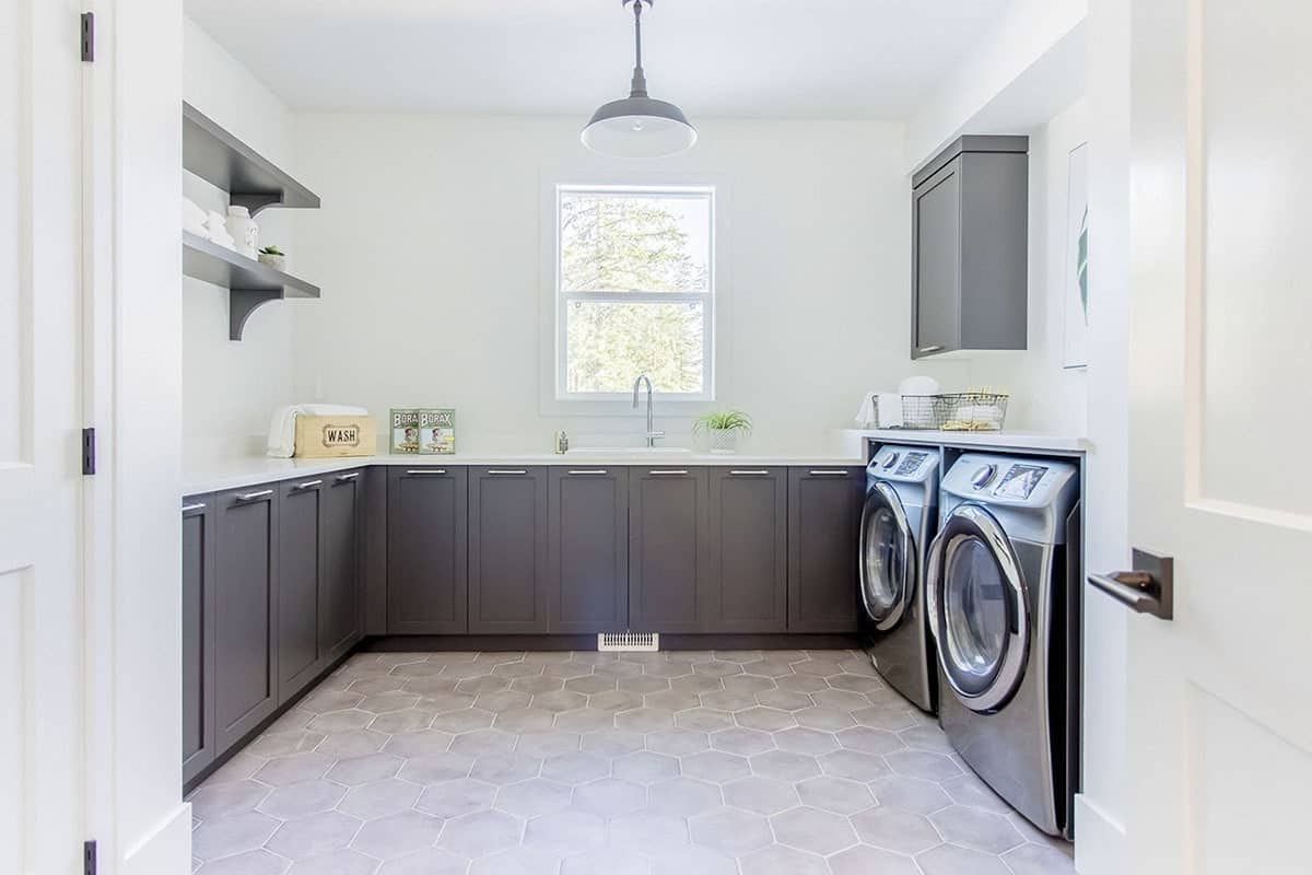 Laundry room with hex tile flooring and gray modular cabinets.