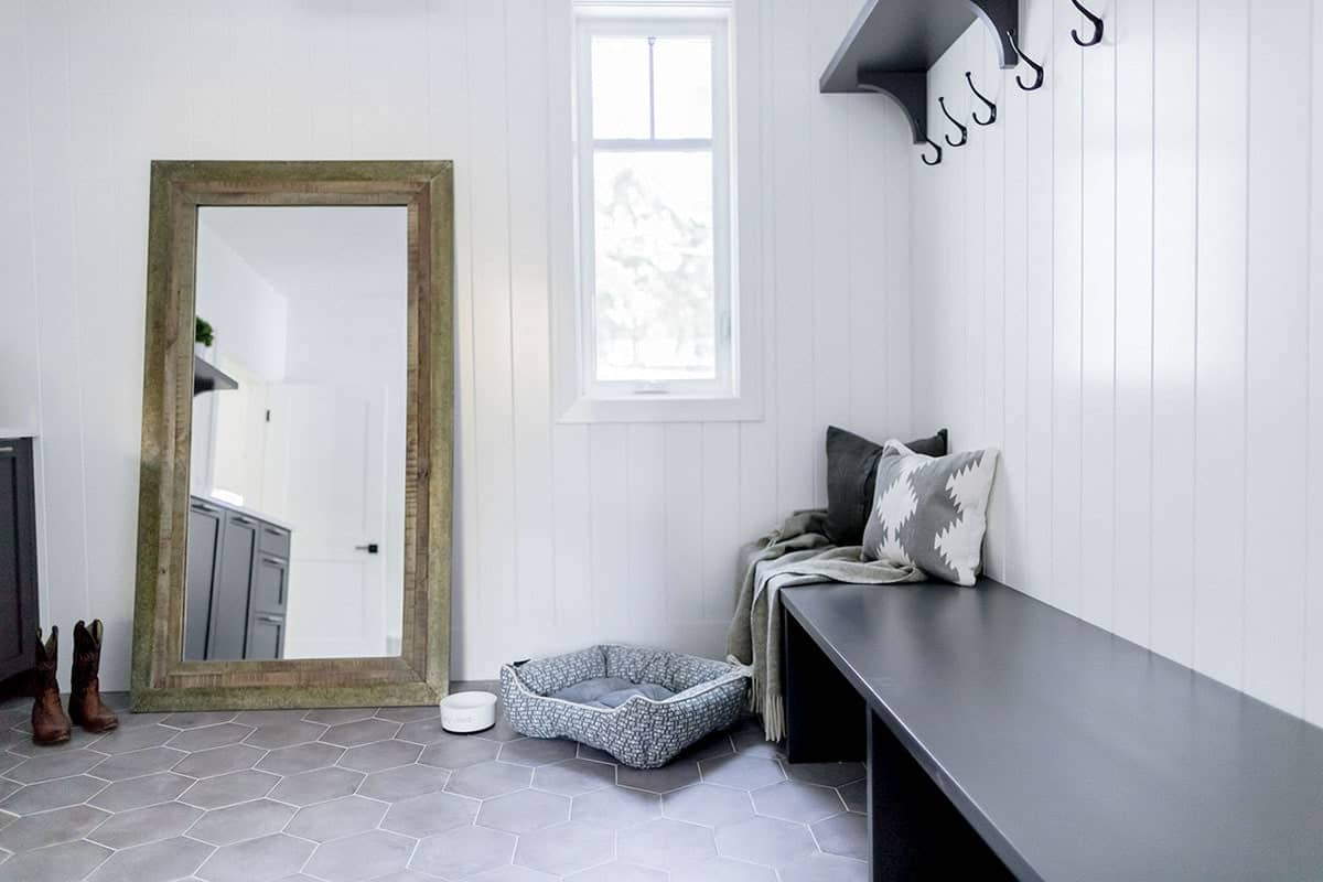 Mudroom with a full-length mirror and built-in bench topped with pillows and throw.