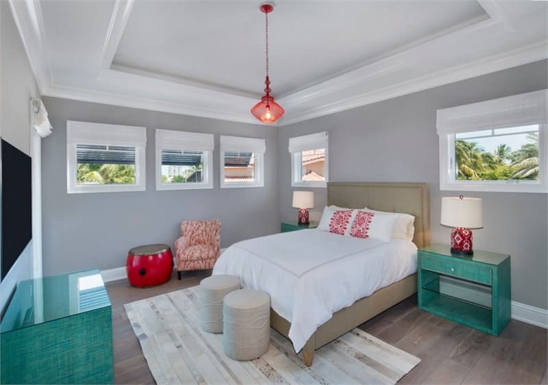 This bedroom has gray walls, natural hardwood flooring, and a tray ceiling with hanging glass pendant.