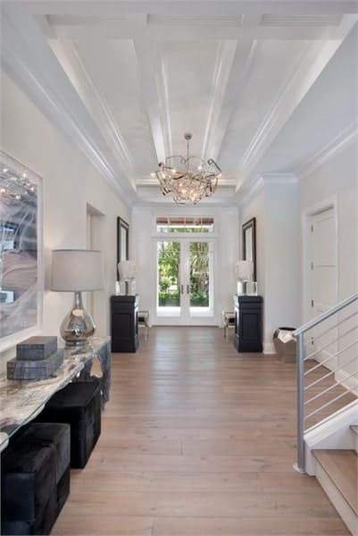 Foyer with natural hardwood flooring and a beamed ceiling mounted with a gorgeous chandelier.